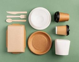 Eco friendly disposable tableware on green background photo