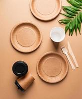 disposable tableware on brown background, flat lay composition photo