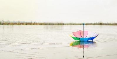 Paraguas de colores del arco iris en charcos en el suelo húmedo de la calle foto