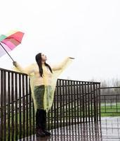 Hermosa mujer morena sosteniendo coloridos paraguas bajo la lluvia foto