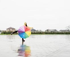 Hermosa mujer morena sosteniendo coloridos paraguas bailando bajo la lluvia foto