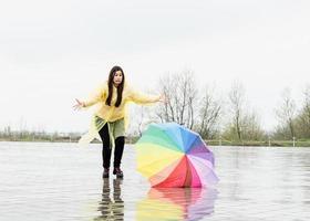 Mujer divertida cogiendo coloridos paraguas al aire libre bajo la lluvia foto