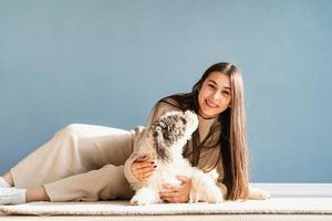 Beautiful woman with playful dog embracing at home photo