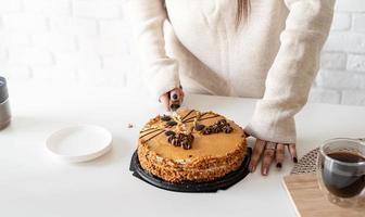 Cerca de manos de mujer cortando un pastel foto