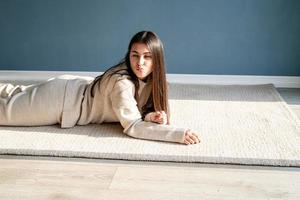 young woman blowing a kiss lying on the rug photo