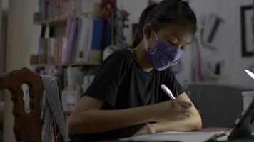 Schoolgirl wears face mask and earphones study for lesson online. video
