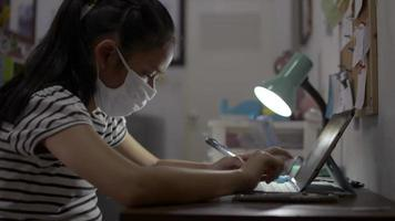 Girl wears face mask studying from home with video call online.