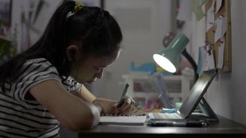 Schoolgirl writing on a book while study from home with lesson online. video