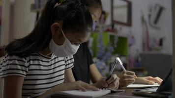 Two girls writing on a desk while study with video call online.