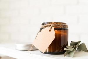 Beautiful burning candle with eucalyptus leaves and craft price tag photo