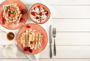 gofres belgas con stawberry fresca sobre fondo blanco de madera. foto