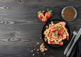 gofres belgas con stawberry fresca sobre fondo de madera oscura. foto