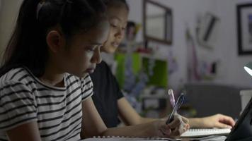 Niñas de la escuela primaria que usan tableta digital para la lección en línea en casa video