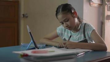 bedårande tjej bär hörlurar studielektion online med digital surfplatta. video