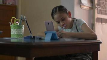 Girl using smartphone and digital tablet for learning lesson online. video