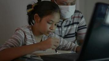 Girl and father wears face mask watching lesson online from laptop. video