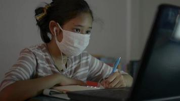 Girl wears face mask and earphones learning lesson online from laptop. video