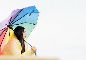 mujer de pie afuera sosteniendo un paraguas de colores del arco iris foto