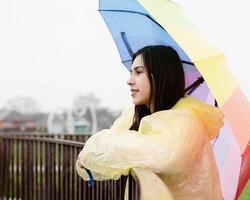 Mujer de pie afuera sosteniendo un paraguas de colores, mirando a otro lado foto
