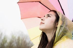 Mujer de pie sosteniendo un paraguas de colores del arco iris, mirando a otro lado foto
