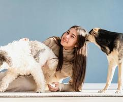 Beautiful woman with playful dogs embracing at home photo
