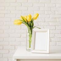 tulipanes amarillos en un jarrón de vidrio y marco de fotos en blanco