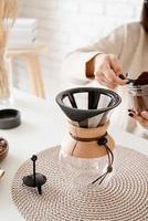 Woman brewing coffee in coffee pot photo