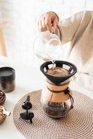Mujer preparando café en una cafetera, vertiendo agua caliente en el filtro foto