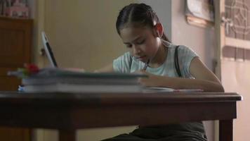 flicka bär hörlurar studielektion online från digital surfplatta hemma. video