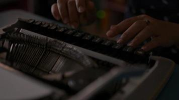 Female office worker typing on retro typewriter on the desk. video