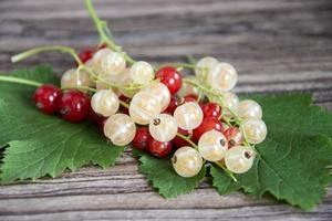 Grosellas rojas y blancas con hojas verdes en un primer plano del montón foto