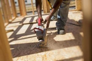 A worker uses a skill saw photo