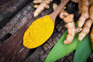 Turmeric powder and fresh turemeric in wooden spoon photo