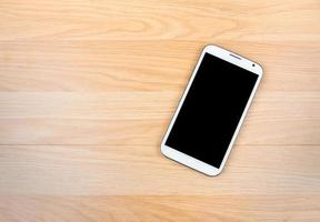 Smart phone on wooden background photo