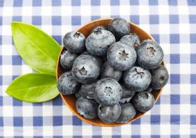 Top view of blueberries in wooden bowls on fabric background photo
