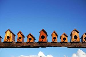 Bird house nesting on blue sky background photo