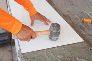Construction worker tiler is tiling photo