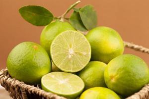 Limón verde fresco en la canasta sobre fondo marrón, lima foto