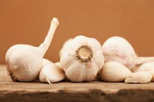 Garlic on old wooden table with brown background photo