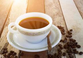 Taza de café con saco de arpillera de granos de café en la mesa de madera foto