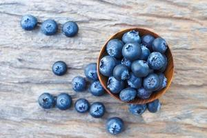 Blueberries in wooden bowls on wooden background photo