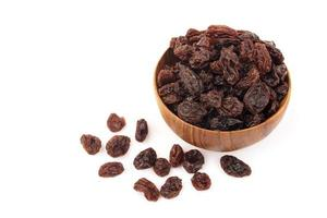 Organic dried Raisins in wooden bowls on white background, Currant photo