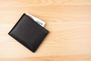 Black wallet with money on brown wood table background photo