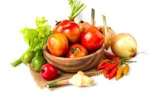 Fruits and vegetables in wooden bowl on white background photo