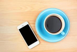 Blue and white coffee cup and smartphone with blank screen photo