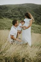Young family with cute little boy having fun outdoors in the field photo