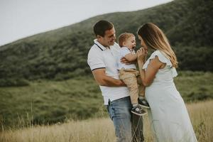 Familia joven con lindo niño divirtiéndose al aire libre en el campo foto
