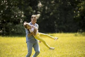 Padre con hija divirtiéndose en el césped del parque foto