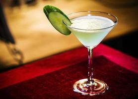 Cucumber and lime martini mixed cocktail drink glass inside cozy bar photo