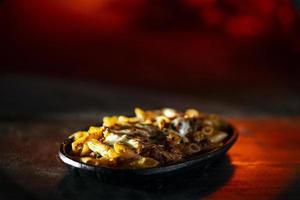 Plato de pasta fresca horneada al horno gourmet penne boloñesa y queso mozzarella foto